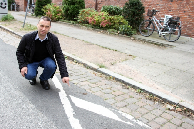 CDU-Bezirksabgeordneter Stefan Baumann zeigt die abgenutzte Farbmarkierung an der Heitmannstraße.